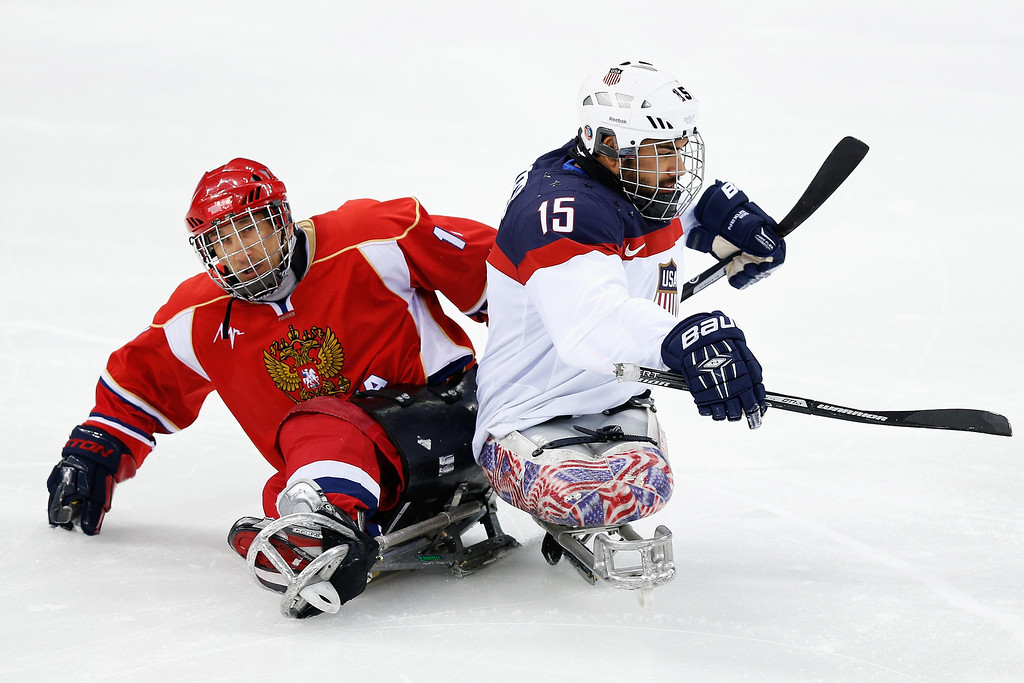 . Nikko Landeros of USA (R) clashes with Alexey Amosov of Russia during the Ice Sledge Hockey Gold Medal match between Russia and USA at the Shayba Arena during day eight of the 2014 Paralympic Winter Games on March 15, 2014 in Sochi, Russia.  (Photo by Harry Engels/Getty Images)