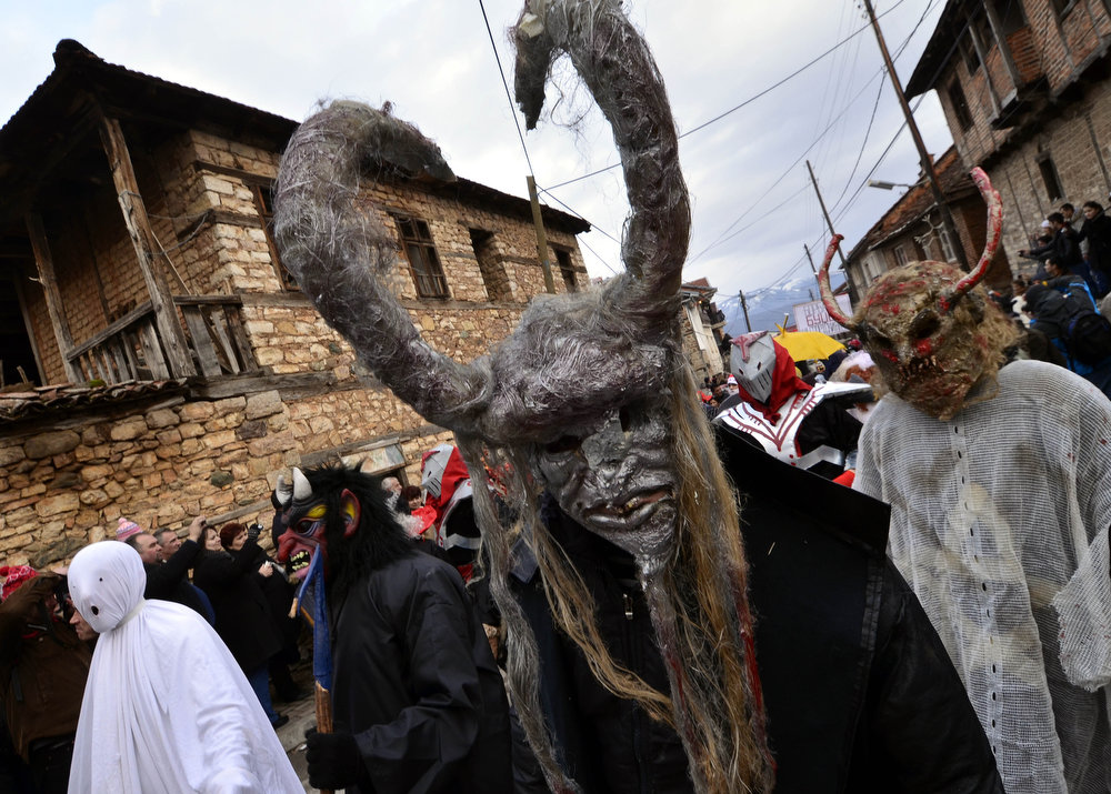 . Masked villagers during the carnival in Vevcani, a small village in southwestern Macedonia, on Sunday, Jan. 13, 2013. The festivities are always held on St. Vasilij\'s day for more than fourteen centuries, marking the arrival of the New Year by the Julian calendar. The carnival which has pagan roots, highlight political satire, with masked local people acting out the current events. (AP Photo/Boris Grdanoski)