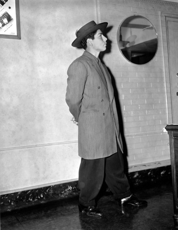 . Frank H. Tellez, 22, who is held on a vagrancy charge, models a zoot suit and pancake hat in a Los Angeles County jail on June 9, 1943. Bands of juvenile zoot suiters have been engaging in rioting with servicemen in Los Angeles. (AP Photo/John T. Burns)