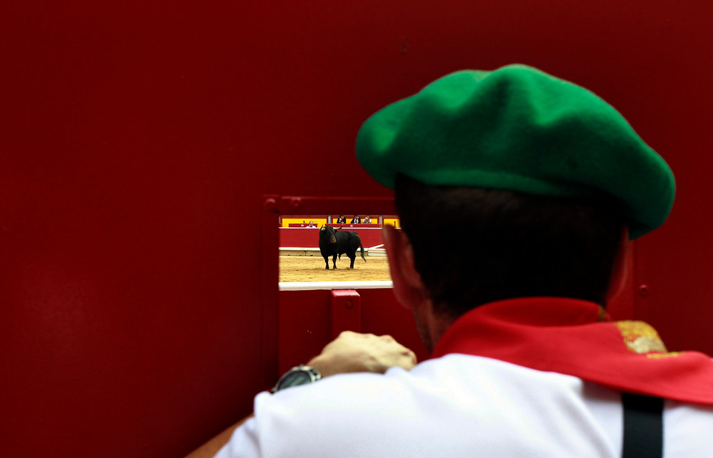 . A bullring worker watches a bull during the fourth bullfight of the San Fermin festival in Pamplona July 10, 2013. REUTERS/Joseba Etxaburu