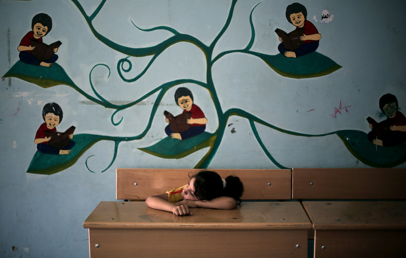 . In this Monday, July 14, 2014 photo, young Palestinian girl Fulla Attar, 10, rests in a classroom of the New Gaza Boys United Nations school, where dozens of families have sought refuge after fleeing their home in fear of Israeli airstrikes. 20 U.N. schools took in more than 17,000 displaced Gazans, many of them children, after Saturday\'s warnings by Israel that civilians must clear out of northern Gaza. (AP Photo/Khalil Hamra)