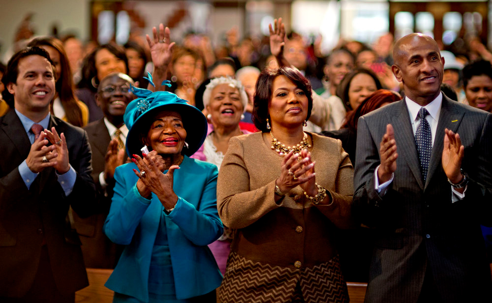 Description of . Bernice King, center right, and Christine King Farris, center left, the daughter and sister of Dr. Martin Luther King Jr., applaud while watching a broadcast as President Barack Obama is inaugurated following the Dr. Martin Luther King Jr. holiday commemorative service at the Ebenezer Baptist Church in Atlanta Monday, Jan. 21, 2013. (AP Photo/David Goldman)