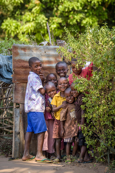Children peer through an open gate to Kapinga's house, next to Nganza Child Friendly Space, Kananga, DRC.