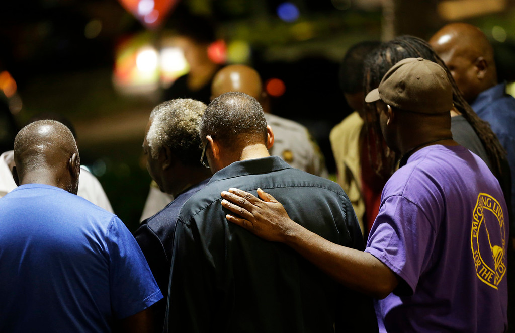 . Worshippers gather to pray in a hotel parking lot across the street from the Emanuel AME Church following a shooting Wednesday, June 17, 2015, in Charleston, S.C. (AP Photo/David Goldman)