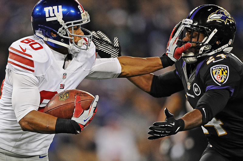 . Wide receiver Victor Cruz #80 of the New York Giants stiff arms cornerback Corey Graham #24 of the Baltimore Ravens in the third quarter at M&T Bank Stadium on December 23, 2012 in Baltimore, Maryland. The Baltimore Ravens won, 33-14.  (Photo by Patrick Smith/Getty Images)