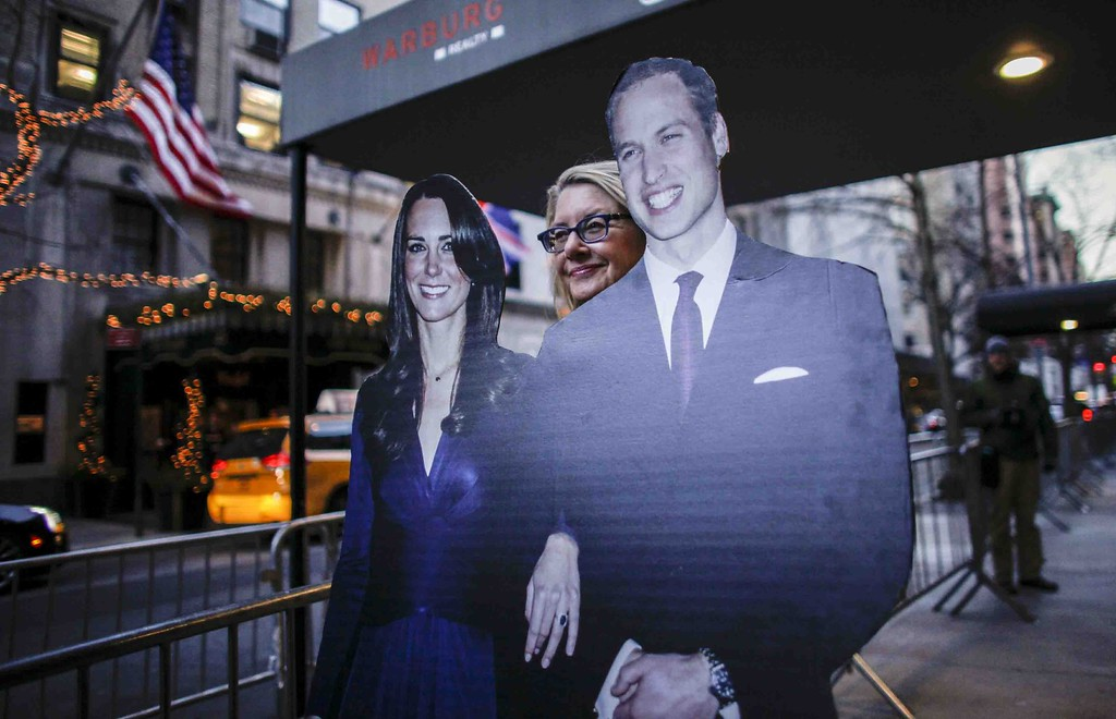 . A woman holds a banner with the image of The Duke and Duchess of Cambridge as she waits their arrival outside their Hotel  on December 07, 2014 in New York.  The three-day US trip will see the Duke and Duchess of Cambridge, both 32, mix diplomacy with supporting their favorite causes and promoting British business interests. KENA BETANCUR/AFP/Getty Images