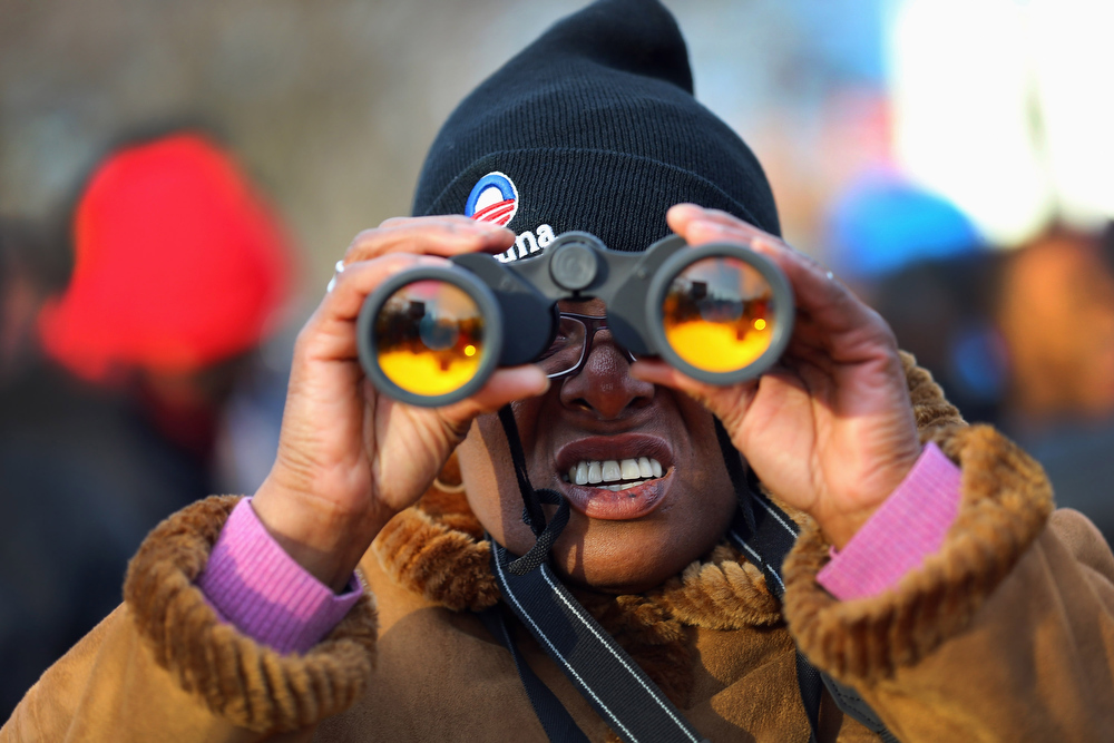 Description of . Ednn Daniels uses binoculars as she and others gather near the U.S. Capitol building on the National Mall for the Inauguration ceremony on January 21, 2013 in Washington, DC.  U.S. President Barack Obama will be ceremonially sworn in for his second term today.  (Photo by Joe Raedle/Getty Images)