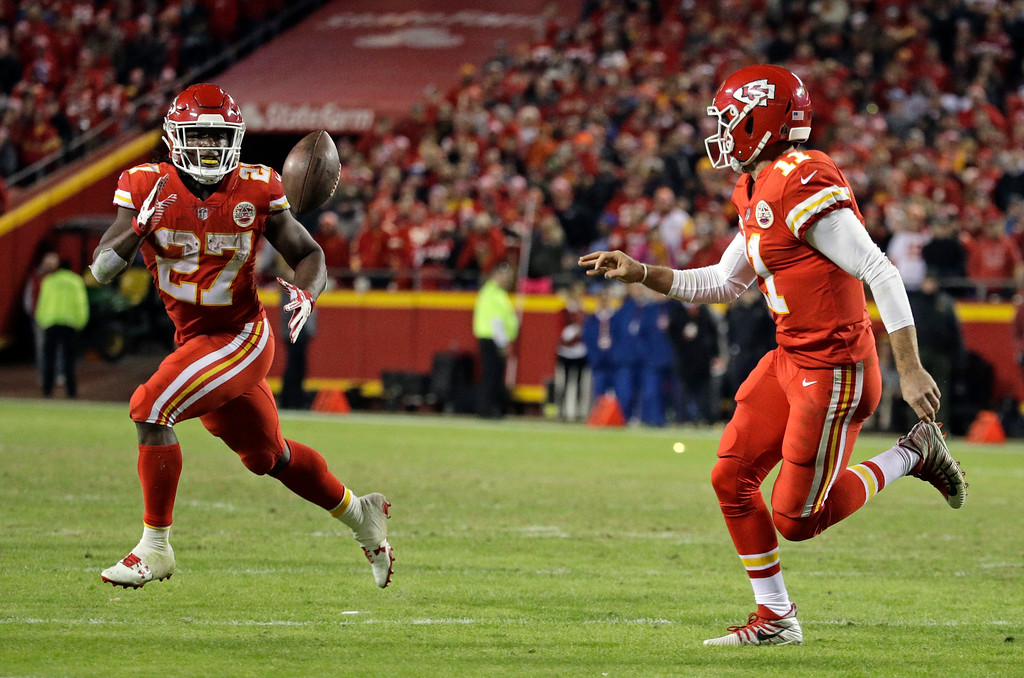 . Kansas City Chiefs quarterback Alex Smith (11) flips the ball to running back Kareem Hunt (27) during the second half of an NFL football game against the Los Angeles Chargers in Kansas City, Mo., Saturday, Dec. 16, 2017. (AP Photo/Charlie Riedel)