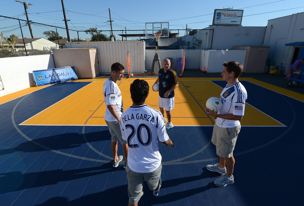. The L.A. Galaxy unveiled a new Sport Court at the Boys and Girls Club of Carson Friday. In December, with the team heading to the championships, the LA Galaxy Foundation announced it would put in the court, donate equipment and host clinics.  Team players Colin Clark, A.J. De La Garza, and Todd Dunivant use the new court to shoot some hoops, with soccer balls, before the unveiling ceremony. 20130301 Photo by Steve McCrank / Staff Photographer