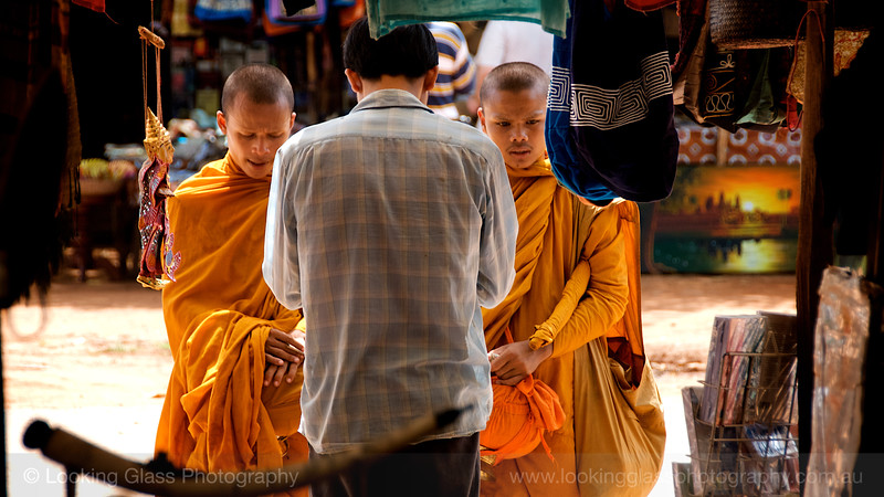 Buddhist Monks receiving donations from shopkeepers