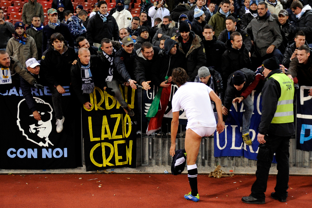 Description of . Lazio's forward Giuseppe Sculli removes his clothes to give as gifts to fans after his UEFA Europa League group D football match against FC Zurich on October 20, 2011 in Zurich. AFP PHOTO / FABRICE COFFRINI