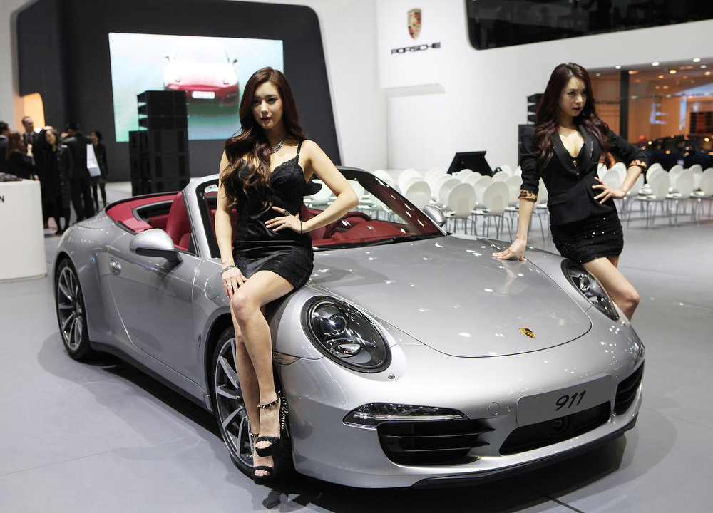 . South Korean models pose with a Porsche 911 during a press day of the Seoul Motor Show in Goyang, South Korea, Thursday, March 28, 2013. The exhibition, with 384 companies from 14 countries to participate, will be held from March 29 through April 7.(AP Photo/Ahn Young-joon)