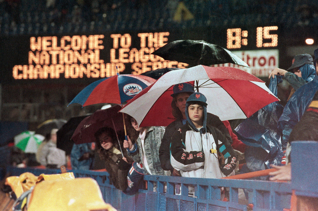 . Fans wait in the rain as the scheduled start of the NL championship series game between the New York Mets and the Los Angeles Dodgers was delayed by inclement weather, Friday, Oct. 7, 1988, New York. (AP Photo/Peter Morgan)