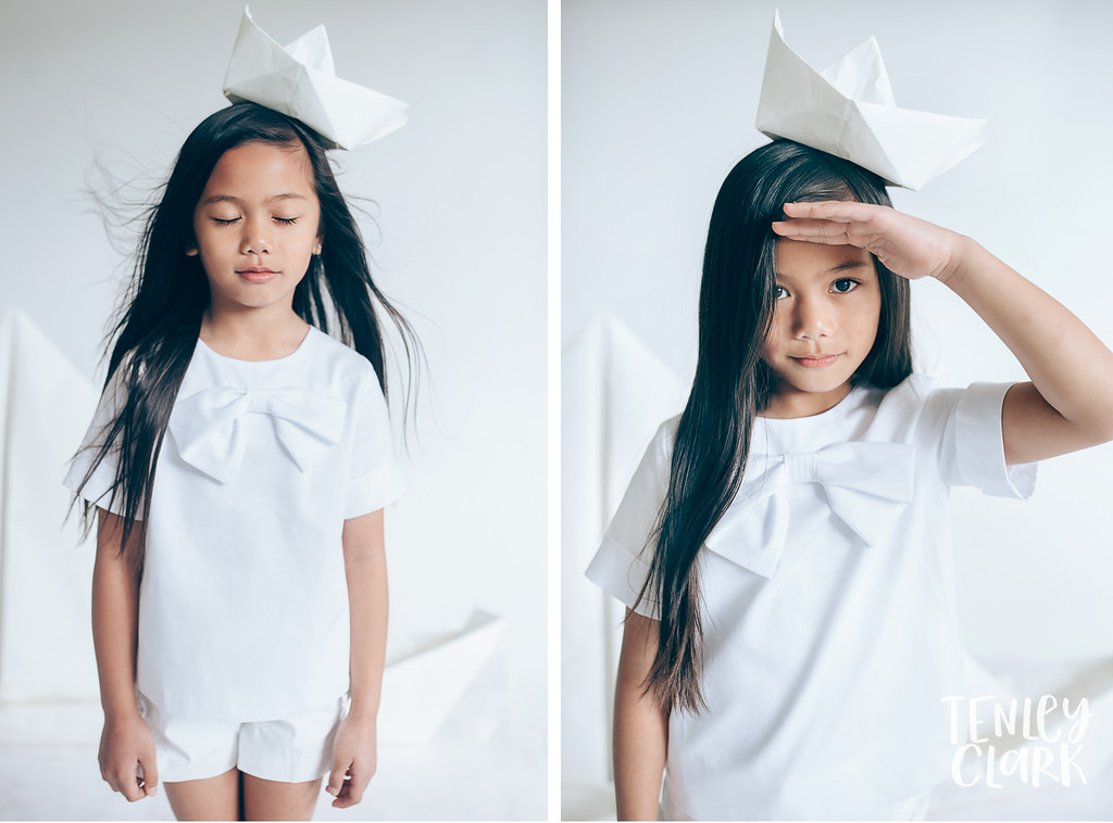 girl with paper sailor hat. Whimsical kid's fashion editorial with giant white paper origami props. Photography by Tenley Clark.