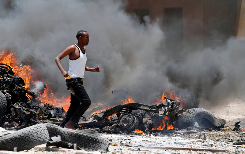 . A man runs through the scene of an explosion near the presidential palace in Somalia\'s capital Mogadishu, March 18, 2013. A car bomb exploded near the presidential palace in the Somali capital Mogadishu on Monday, killing at least 10 people in a blast that appeared to target senior government officials, police said. REUTERS/Feisal Omar