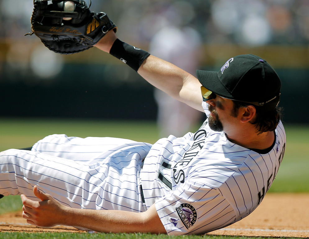 . Colorado Rockies\' Todd Helton keeps control of a throw from third baseman Nolan Arenado, allowing Arizona Diamondbacks\' A.J. Pollock by for a single during the fifth the inning of a baseball game Wednesday, May 22, 2013 in Denver. The Rockies won 4-1. (AP Photo/Barry Gutierrez)