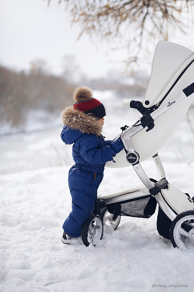 Mima_Xari_Lifestyle_Snow_White_Aluminium_Chassis_Pod_Baby_Looking_At_Pushchair_In_Snow.jpg