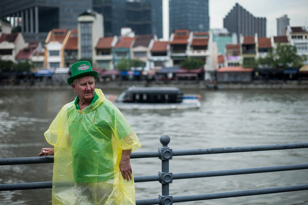 . A man waits for the parade to start during the Singapore St. Patricks Day Street Festival at Boat Quay on March 17, 2013 in Singapore. Singapore\'s Irish community gathered at Boat Quay for a three-day-long St Patrick\'s Day Street Festival which featured street performances, buskers, and Irish food and drink.  (Photo by Chris McGrath/Getty Images)