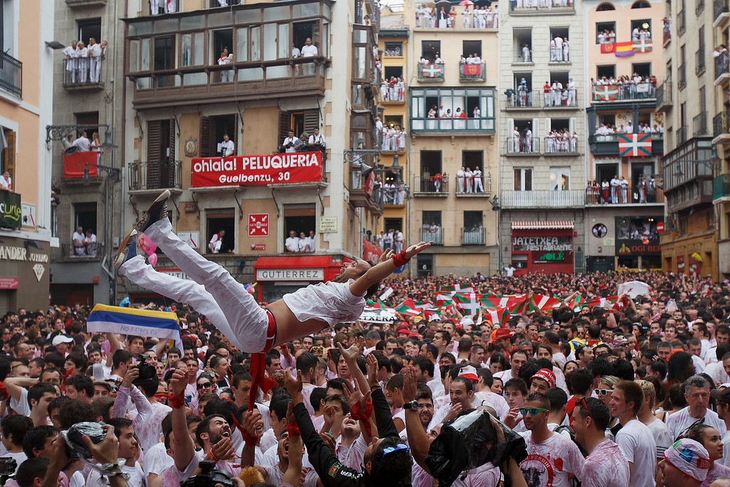 . Thousands of revellers sing and dance during the opening and the firing of the \'Chupinazo\' rocket which starts the 2014 Festival of the San Fermin Running of the Bulls on July 6, 2014 in Pamplona, Spain. The annual Fiesta de San Fermin, made famous by the 1926 novel of US writer Ernest Hemmingway entitled \'The Sun Also Rises\', involves the daily running of the bulls through the historic heart of Pamplona to the bull ring.  (Photo by Pablo Blazquez Dominguez/Getty Images)