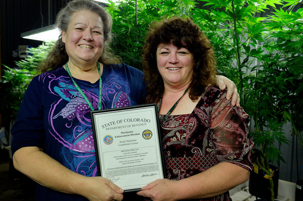 . NORTHGLENN, CO. - DECEMBER 31: (l-r) Sisters, Robin and Cheri Hackett pose for a portrait with their retail marijuana license at BotanaCare 21+ in Northglenn, CO December 31, 2013. The co-owners were preparing to open at 9am on January 1, 2014 when Colorado becomes the first place anywhere in the world to allow legal marijuana sales to anybody over 21 for any purpose. (Photo By Craig F. Walker / The Denver Post)