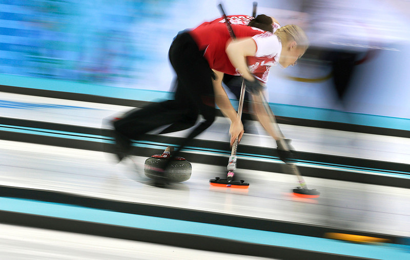 . Russia\'s Alexandra Saitova, foreground, and Ekaterina Galkina, sweep the ice during the women\'s curling competition against the United States at the 2014 Winter Olympics, Tuesday, Feb. 11, 2014, in Sochi, Russia. (AP Photo/Wong Maye-E)