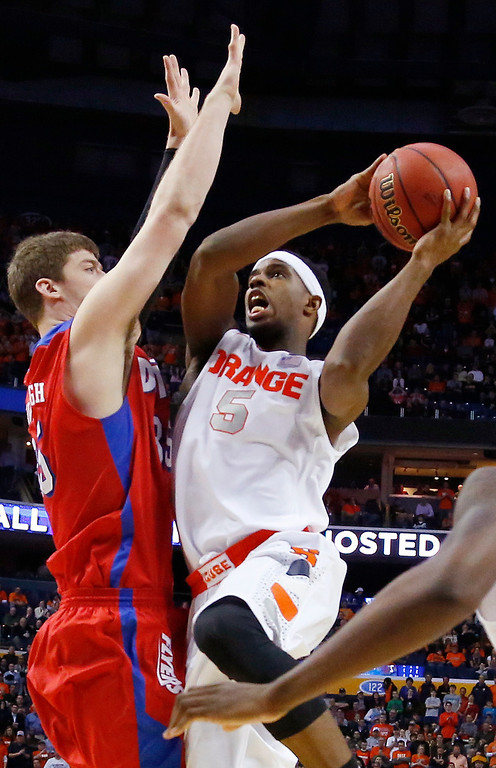 . Syracuse\'s C.J. Fair (5) shoots over Dayton\'s Matt Kavanaugh (35) during the first half of a third-round game in the NCAA men\'s college basketball tournament in Buffalo, N.Y., Saturday, March 22, 2014. (AP Photo/Bill Wippert)