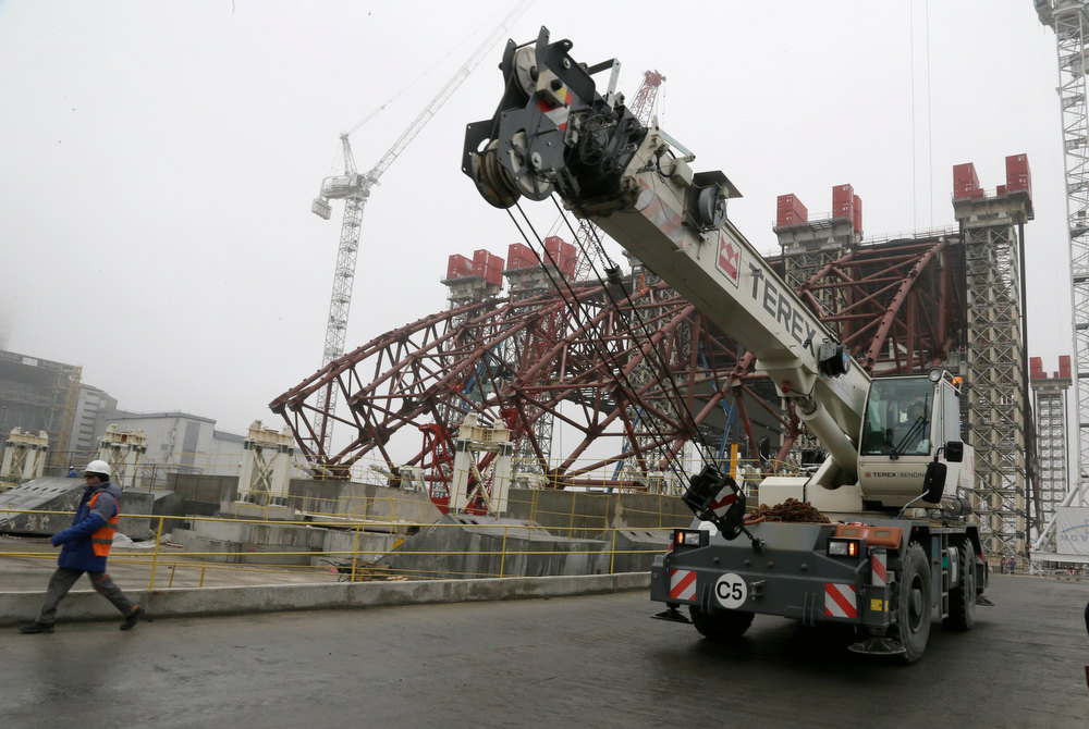. Construction workers assist in the assembly of a gigantic steel-arch to cover the remnants of the exploded reactor at the Chernobyl nuclear power plant in Chernobyl, Ukraine, Tuesday, Nov. 27, 2012. The new safe confinement, a structure that is being built over reactor 4, left, damaged in 1986 as a result of the world\'s worst nuclear accident, will cover a hastily built sarcophagus, which was erected shortly after the explosion. (AP Photo/ Efrem Lukatsky)