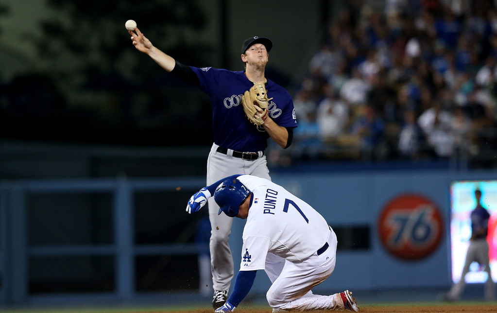 . LOS ANGELES, CA - JULY 12:  Second baseman DJ LeMahieu #9 of the Colorado Rockies throws to first to complete a double play after forcing out Nick Punto #7 of the Los Angeles Dodgers in the eighth inning at Dodger Stadium on July 12, 2013 in Los Angeles, California.  (Photo by Stephen Dunn/Getty Images)