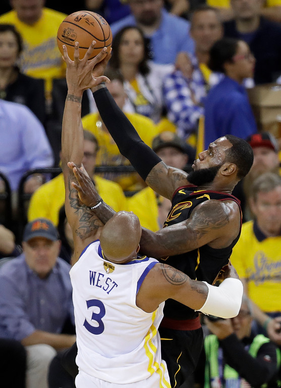 . Cleveland Cavaliers forward LeBron James, right, shoots against Golden State Warriors forward David West (3) during the first half of Game 1 of basketball\'s NBA Finals in Oakland, Calif., Thursday, May 31, 2018. (AP Photo/Marcio Jose Sanchez)