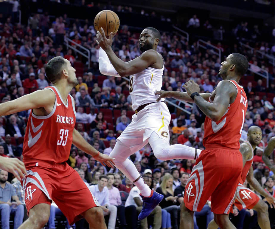. Cleveland Cavaliers guard Dwyane Wade (9) goes up to pass between Houston Rockets forward Ryan Anderson (33) and forward Trevor Ariza (1) during the first half of an NBA basketball game Thursday, Nov. 9, 2017, in Houston. (AP Photo/Michael Wyke)