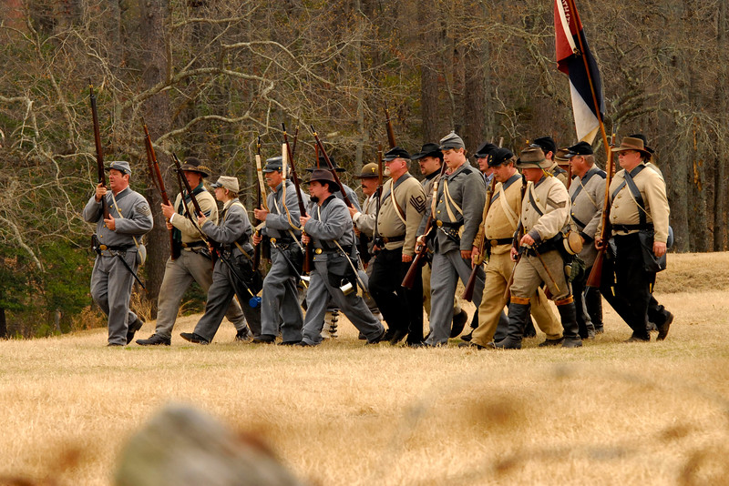 Confederate infantry reenactors march across the field to push back the Union line. The Skirmish at Gamble's Hotel happened on March 5, 1885 when 500 federal soldiers, under the command of Reuben Williams of the 12th Indiana Infantry, marched into Florence to destroy the railroad depot but were met by Confederate soldiers backed up with 400 militia. The reenactment, held by the 23rd South Carolina Infantry, was held at the Rankin Plantation in Florence, South Carolina on Saturday, March 5, 2011. Photo Copyright 2011 Jason Barnette