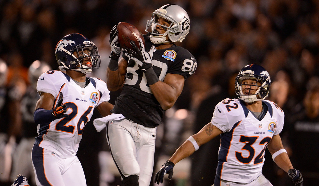 . Oakland Raiders wide receiver Rod Streater (80) catches a deep pass on Denver Broncos free safety Rahim Moore (26) and Denver Broncos defensive back Tony Carter (32) in the first quarter Thursday, December 6, 2012 during Thursday Night Football at O.c Coliseum in Oakland  John Leyba, The Denver Post