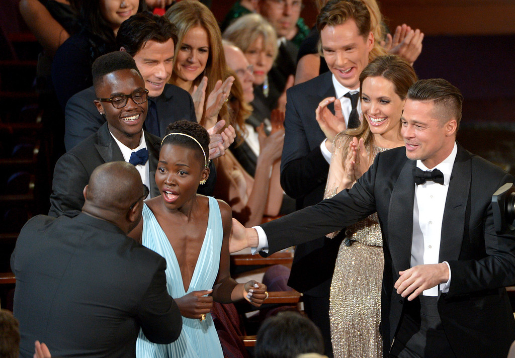 ". Director Steve McQueen, left, congratulates Lupita Nyong\'o on her win for best actress in a supporting role for ""12 Years a Slave\"" as,  from background left, her brother Peter, John Travolta, Kelly Preston, Benedict Cumberbatch, Angelina Jolie, and Brad Pitt look on during the Oscars at the Dolby Theatre on Sunday, March 2, 2014, in Los Angeles.  (Photo by John Shearer/Invision/AP)"