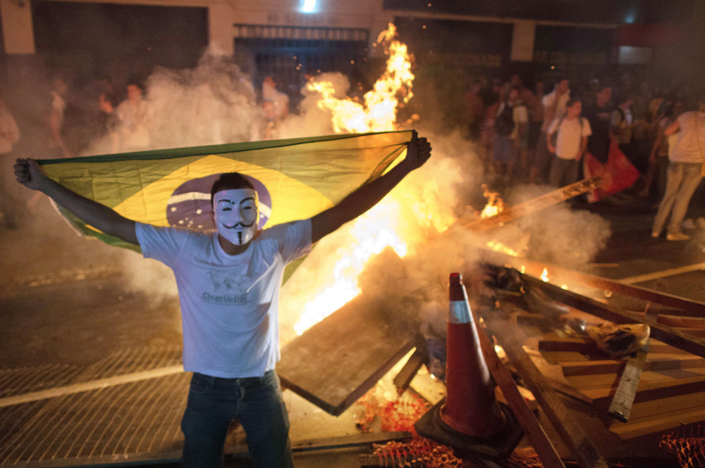 . A demonstrator holds a flag late on June 19, 2013 during clashes in the center of Niteroi, 10 kms from Rio de Janeiro. Protesters battled police late on June 19, even after Brazil\'s two biggest cities rolled back the transit fare hikes that triggered two weeks of nationwide protests.  The fare rollback in Sao Paulo and Rio de Janeiro marked a major victory for the protests, which are the biggest Brazil has seen in two decades.  CHRISTOPHE SIMON/AFP/Getty Images