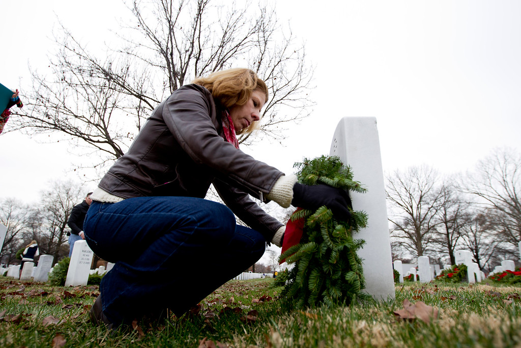 . Ann McCampbell  lay holiday wreaths over the grave of her uncle Navy Capt. David McCampbell at Arlington National Cemetery in Arlington, Va., Saturday Dec. 14, 2013, during Wreaths Across America Day. Wreaths Across America was started in 1992 at Arlington National Cemetery by Maine businessman Morrill Worcester and has expanded to hundreds of veterans\' cemeteries and other locations in all 50 states and beyond. (AP Photo/Jose Luis Magana)