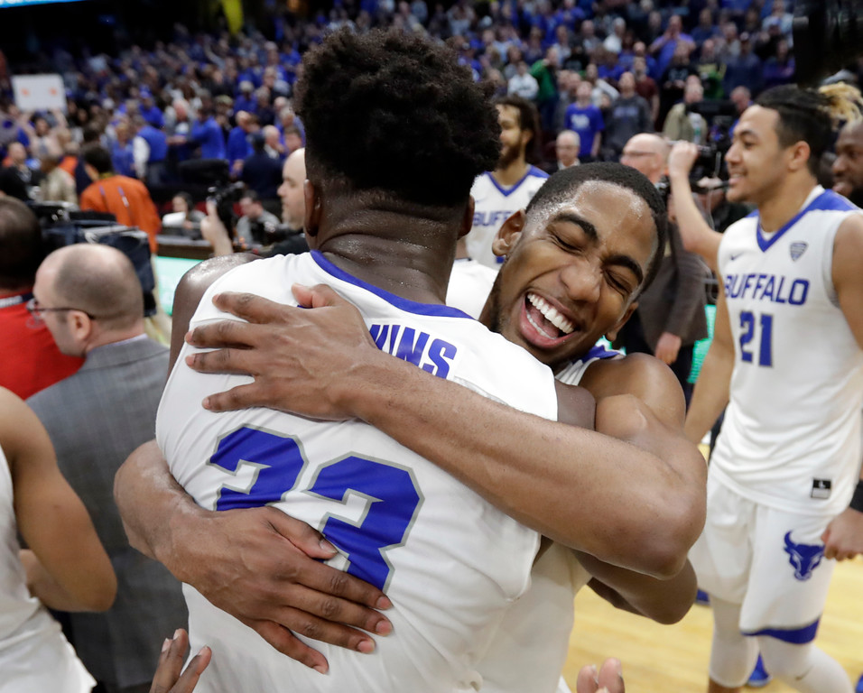 . Buffalo\'s CJ Massinburg, right, hugs Nick Perkins after Buffalo defeated Toledo 76-66 in an NCAA college basketball championship game of the Mid-American Conference tournament, Saturday, March 10, 2018, in Cleveland. (AP Photo/Tony Dejak)