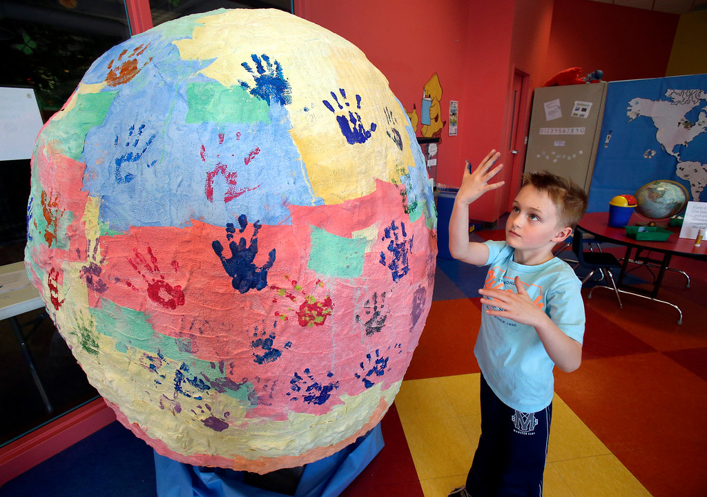 . Matthew Baumann, 7, looks at his painted hand after placing it on a giant paper mache globe at The Building for Kids Children\'s Museum, Tuesday, April 22, 2014, in Appleton, Wis. Children made handprints to show they were lending a hand to help the earth. According to Gwen Schmitt, education coordinator, along with the globe, there were a variety of stations related to earth conscious activities. (AP Photo/The Post-Crescent, Dan Powers)