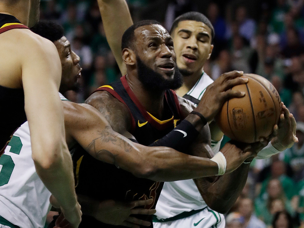 . Cleveland Cavaliers forward LeBron James drives against Boston Celtics guard Marcus Smart, left, and forward Jayson Tatum, right, during the first quarter of Game 5 of the NBA basketball Eastern Conference finals Wednesday, May 23, 2018, in Boston. (AP Photo/Charles Krupa)