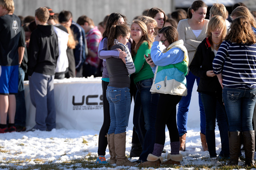 . CENTENNIAL, CO - Students on their phones to their parents as they stand out side on the football field after a gunman was spotted inside Arapahoe High School December 13, 2013. The gunman was targeting a teacher at the school. The gunman shot two students in the process and then turned the gun on himself. (Photo by John Leyba/The Denver Post)
