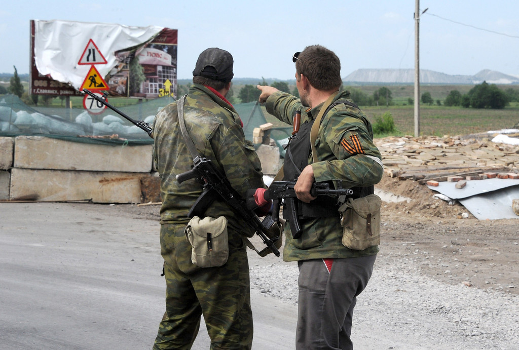 . Pro-Russian armed militants point at a position manned by Ukrainian army soldiers near the eastern Ukrainian city of Slavyansk, Donetsk region, on May 23, 2014. Russian President Vladimir Putin said today that the crisis in Ukraine had evolved into a full-scale civil war, blaming Washington for backing the overthrow of former president Viktor Yanukovych. AFP PHOTO / VIKTOR DRACHEV/AFP/Getty Images