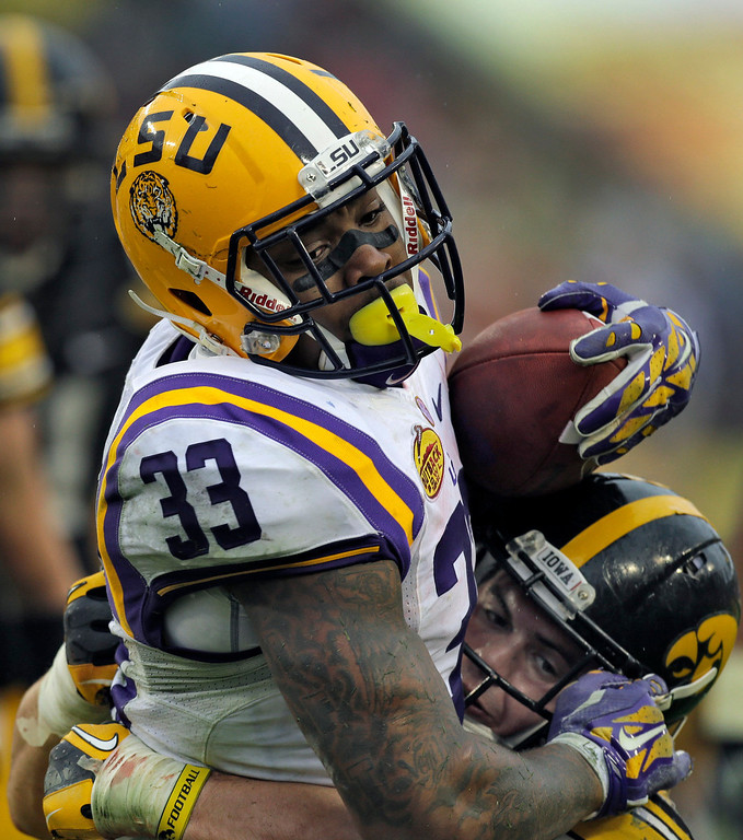. LSU running back Jeremy Hill (33) carries Iowa linebacker James Morris (44) into the end zone to score on a 14-yard touchdown run during the second quarter of the Outback Bowl NCAA college football game Wednesday, Jan. 1, 2014, in Tampa, Fla. (AP Photo/Chris O\'Meara)