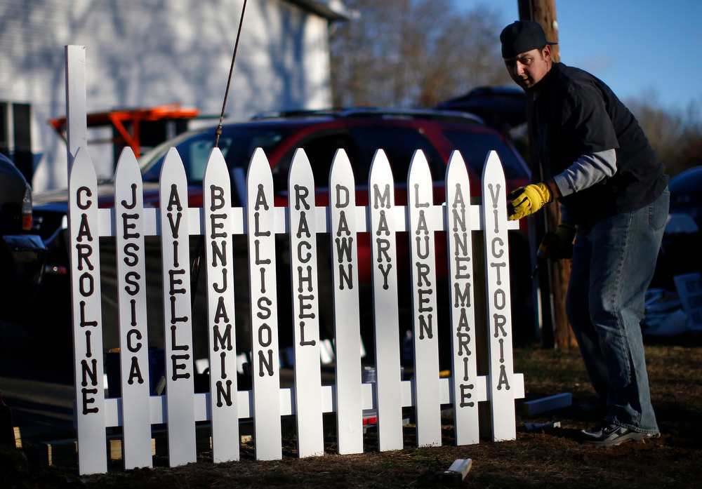 Description of . Mike Garbowski of Newtown, Connecticut begins to erect a fence he built that will bear the names of all of those killed in the December 14 shootings at the Sandy Hook Elementary School in Sandy Hook village in Newtown, December 19, 2012. Six funerals for victims of the shootings were being held Wednesday in the Newtown area. REUTERS/Mike Segar