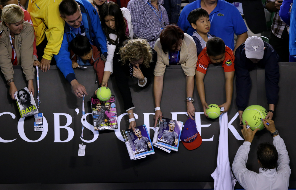 . Rafael Nadal of Spain signs autographs for fans after defeating Roger Federer of Switzerland in their semifinal at the Australian Open tennis championship in Melbourne, Australia, Friday, Jan. 24, 2014. (AP Photo/Aaron Favila)