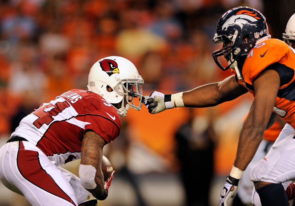 . ARIZONA CARDINALS - Denver Broncos defense grabs the face mask of Arizona Cardinals running back Ryan Williams (34)  during a pre-season NFL football game on Thursday, Aug. 29, 2013, in Denver. (AP Photo/Jack Dempsey)