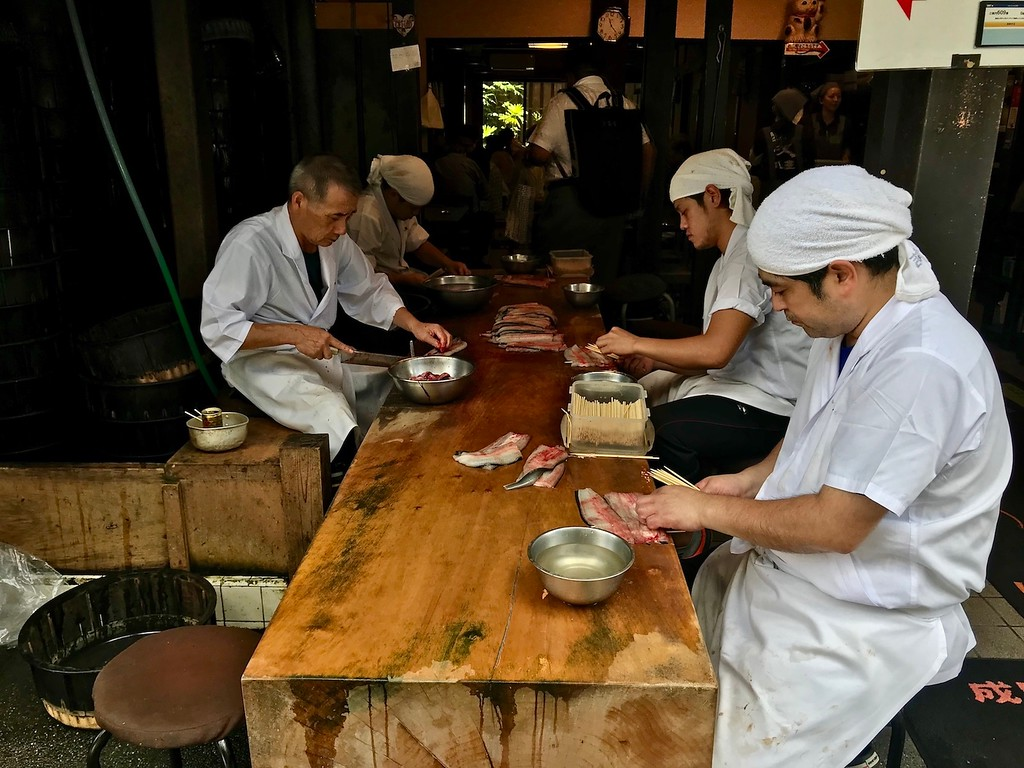 Chefs preparing eel for rice bowls.