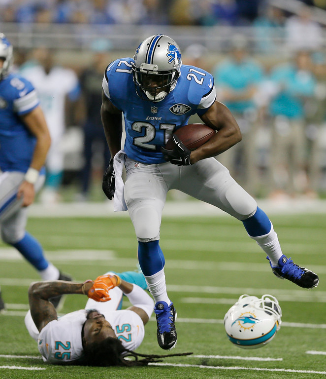 . Detroit Lions running back Reggie Bush (21) jumps over Miami Dolphins free safety Louis Delmas (25) for a gain during the first half of an NFL football game in Detroit, Sunday, Nov. 9, 2014. (AP Photo/Carlos Osorio)
