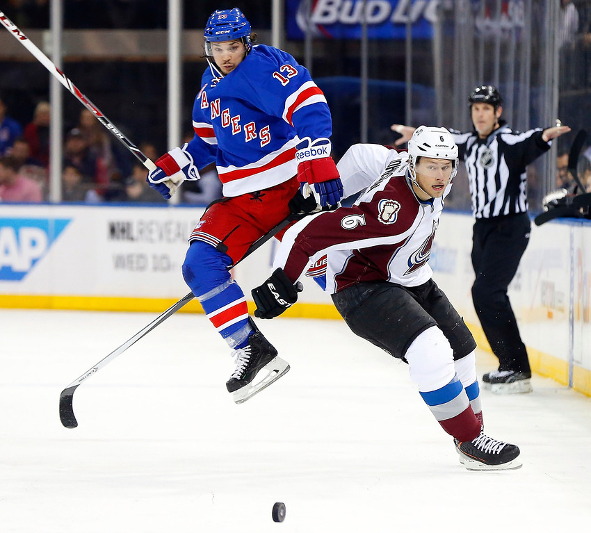 . Daniel Carcillo #13 of the New York Rangers tries to leap past Erik Johnson #6 of the Colorado Avalanche during the second period at Madison Square Garden on February 4, 2014 in New York City.  (Photo by Jim McIsaac/Getty Images)