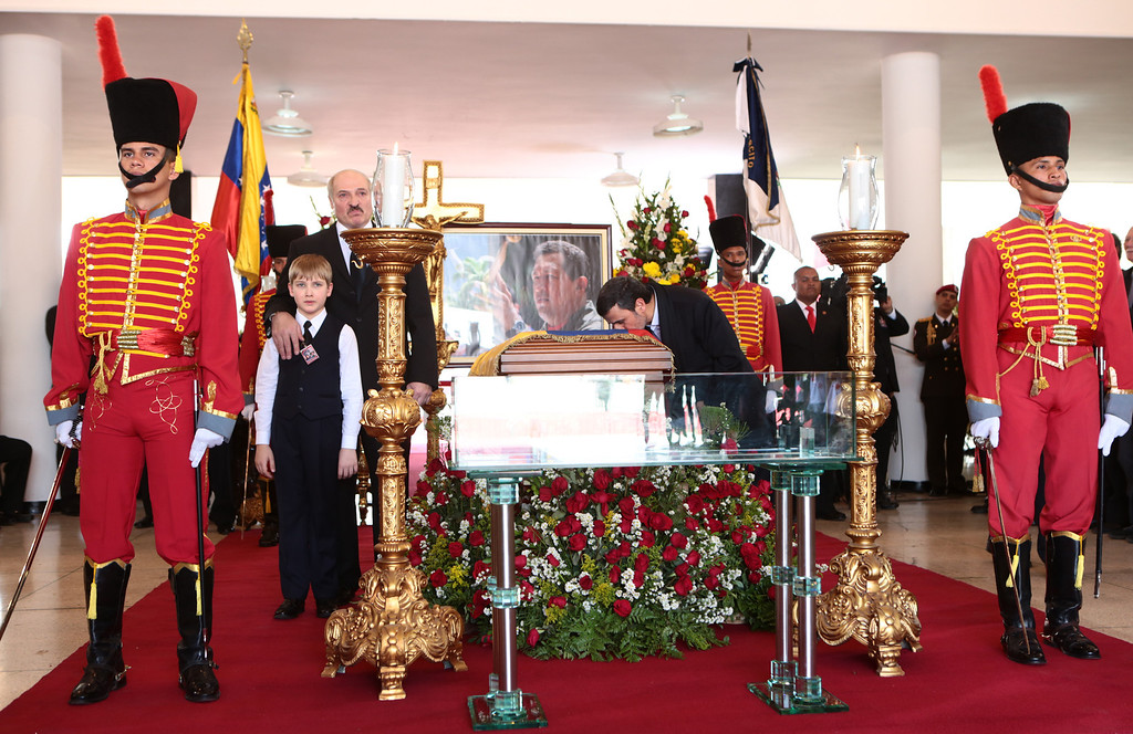 . Handout picture released by the Venezuelan presidency showing Iran\'s President Mahmoud Ahmadinejad kissing the coffin of Venezuelan President Hugo Chavez as President Alexander Lukashenko of Belarus and his son stand next to it during the funeral of the late Venezuelan leader, in Caracas, on March 8, 2013.   AFP PHOTO/PRESIDENCIA/HO /AFP/Getty Images
