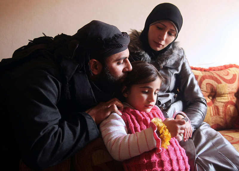 . Um Jaafar, a woman fighter in the Free Syrian Army, sits with her husband Abu Jaafar, a Sawt al-Haq (Voice of Rights) battalion commander, and her daughter Faten at their home in Aleppo February 12, 2013. Um Jaafar was a women\'s hairdresser before the revolution and after being trained by her husband she is now a member of a Sawt al-Haq battalion on the frontline of Aleppo\'s Sheikh Saeed neighbourhood. REUTERS/Muzaffar Salman
