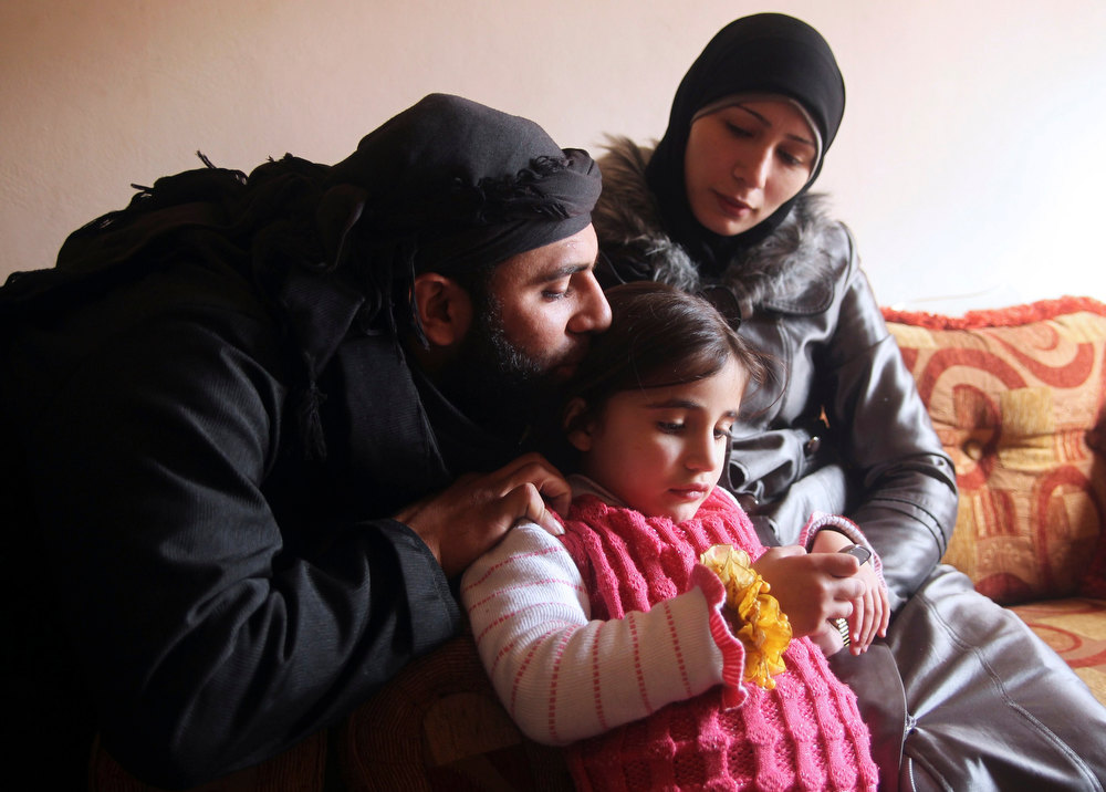 Description of . Um Jaafar, a woman fighter in the Free Syrian Army, sits with her husband Abu Jaafar, a Sawt al-Haq (Voice of Rights) battalion commander, and her daughter Faten at their home in Aleppo February 12, 2013. Um Jaafar was a women's hairdresser before the revolution and after being trained by her husband she is now a member of a Sawt al-Haq battalion on the frontline of Aleppo's Sheikh Saeed neighbourhood. REUTERS/Muzaffar Salman